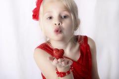 Kleines Mädchen, das einen Kuss mit einem Herzen in ihrer Hand durchbrennt. Lizenzfreie Stockbilder