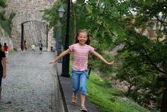 Kleines Mädchen, das in einen Park läuft und lächelt Stockfotografie