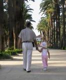 Kleines Mädchen, das in einen Park mit ihrem Großvater geht stockbilder