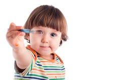 Kleines Mädchen, das einen Pinsel anhält Stockfoto