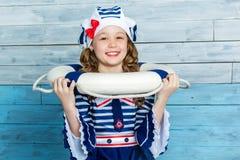 Kleines Mädchen, das einen Rettungsring und ein Lachen hält Stockbilder