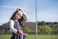 Kleines Mädchen, das einen Roller auf eine Sportanlage reitet Stockfoto
