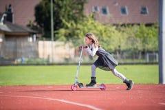 Kleines Mädchen, das einen Roller auf eine Sportanlage reitet Stockfotos
