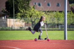 Kleines Mädchen, das einen Roller auf eine Sportanlage reitet Stockfotografie