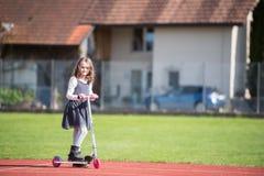 Kleines Mädchen, das einen Roller auf eine Sportanlage reitet Lizenzfreie Stockbilder