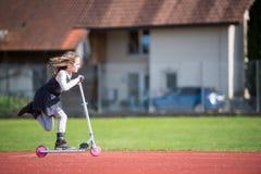 Kleines Mädchen, das einen Roller auf eine Sportanlage reitet Lizenzfreies Stockfoto