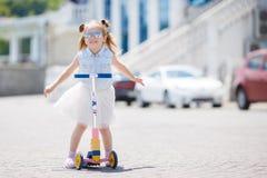 Kleines Mädchen, das einen Roller in der Stadt reitet Stockbilder