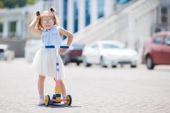 Kleines Mädchen, das einen Roller in der Stadt reitet Lizenzfreie Stockfotografie