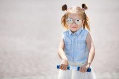 Kleines Mädchen, das einen Roller in der Stadt reitet Lizenzfreie Stockfotos