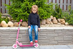 Kleines Mädchen, das einen Roller in ihrem Yard reitet Stockfotos