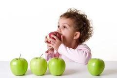 Kleines Mädchen, das einen roten Apfel isst Lizenzfreies Stockfoto