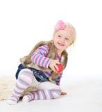 Kleines Mädchen, das einen roten Apfel sitzt auf dem Boden hält Lizenzfreie Stockbilder