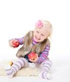 Kleines Mädchen, das einen roten Apfel sitzt auf dem Boden hält Stockbild