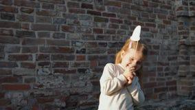 Kleines Mädchen, das einen roten Hut auf einem Stock, stehend nahe bei einem Ziegelstein wal hält stock video