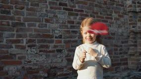 Kleines Mädchen, das einen roten Hut auf einem Stock, stehend nahe bei einem Ziegelstein wal hält stock footage