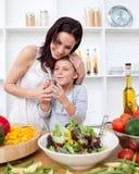 Kleines Mädchen, das einen Salat mit ihrer Mutter zubereitet Stockfotografie