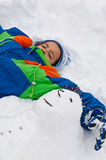 Kleines Mädchen, das einen Schneemann umarmt Lizenzfreies Stockbild