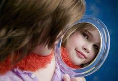 Kleines Mädchen, das einen Spiegel schaut Stockfoto