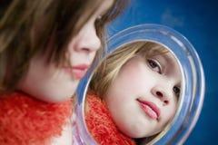 Kleines Mädchen, das einen Spiegel schaut Stockbilder