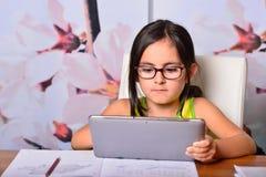 Kleines Mädchen, das einen Tablet-PC für Hausarbeit verwendet Stockfotografie