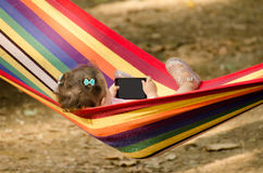 Kleines Mädchen, das in einer Hängematte sich entspannt Stockfotos