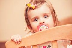 Kleines Mädchen, das in einer Krippe mit sitzt Übertragung stockbilder