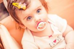 Kleines Mädchen, das in einer Krippe mit sitzt Übertragung lizenzfreies stockfoto