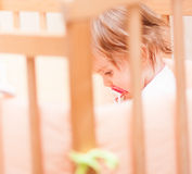 Kleines Mädchen, das in einer Krippe mit sitzt Lizenzfreie Stockfotos