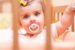 Kleines Mädchen, das in einer Krippe mit sitzt Stockbilder