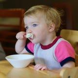 Kleines Mädchen, das Eiscreme im Restaurant isst Stockfotos