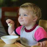 Kleines Mädchen, das Eiscreme im Restaurant isst Lizenzfreie Stockbilder