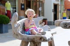Kleines Mädchen, das Eistüte in der Stadt isst Stockbild