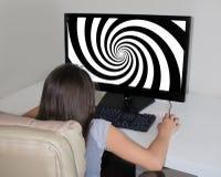 Kleines Mädchen, das entlang der Hypnosespirale auf der Großleinwand ihres Computers anstarrt Lizenzfreie Stockbilder