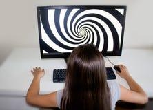 Kleines Mädchen, das entlang der Hypnosespirale auf ihrem Computer anstarrt Lizenzfreie Stockfotografie