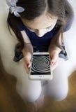 Kleines Mädchen, das entlang der Hypnosespirale an ihrem Handy anstarrt Stockfoto