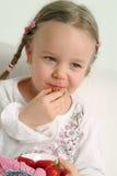Kleines Mädchen, das Erdbeere isst Stockfotos