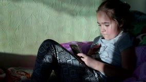 Kleines Mädchen, das erhitzt zu Hause mit Telefon spielt Kind-` s Abhängigkeit auf Geräten stock footage