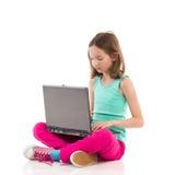 Kleines Mädchen, das etwas auf einem Laptop schreibt Stockbild
