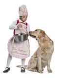 Kleines Mädchen, das für ihren Hund kocht Stockfotos