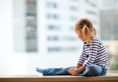 Kleines Mädchen, das Fenster betrachtet Stockfotografie