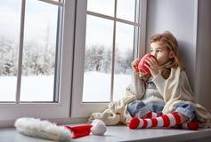 Kleines Mädchen, das am Fenster sitzt Stockfotos