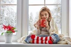 Kleines Mädchen, das am Fenster sitzt Lizenzfreies Stockfoto