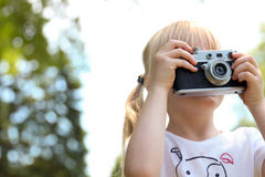 Kleines Mädchen, das Foto unter Verwendung der Weinlesefilmkamera macht Stockfotos