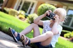 Kleines Mädchen, das Foto unter Verwendung der Weinlesefilmkamera macht Stockfotografie