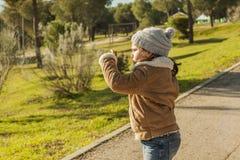 Kleines Mädchen, das Fotos mit einem Smartphone macht Stockfotos