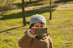 Kleines Mädchen, das Fotos mit einem Smartphone macht Lizenzfreie Stockbilder