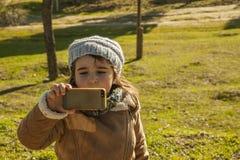 Kleines Mädchen, das Fotos mit einem Smartphone macht Stockfoto