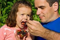 Kleines Mädchen, das Früchte isst Stockfotos