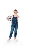 Kleines Mädchen, das Fußball hält und Daumen herauf Zeichen zeigt lizenzfreie stockbilder