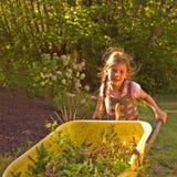 Kleines Mädchen, das gelbe Schubkarre verwendet Lizenzfreie Stockbilder